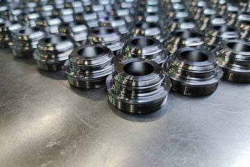 a batch of shiny metal cnc aerospace parts production - close-up with selective focus for industrial background composition